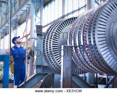Engineer lifting high pressure steam turbine with crane in workshop - Stock Photo