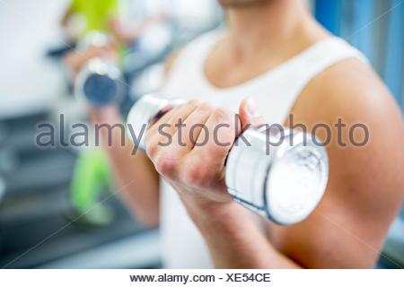 PROPERTY RELEASED. MODEL RELEASED. Young man holding dumbbells while work out, close-up. - Stock Photo