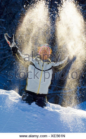 woman throwing snow up into the air, France - Stock Photo