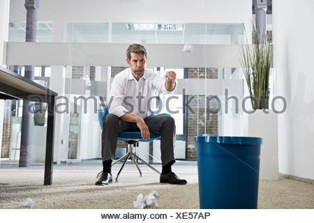 Businessman in office throwing crumpled paper in wastepaper basket - Stock Photo