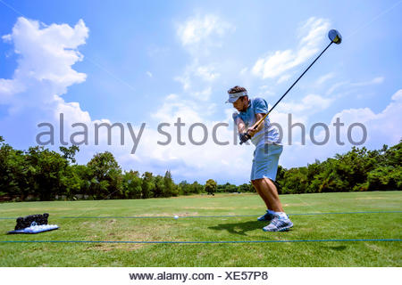 Young man playing golf, Bali, Indonesia - Stock Photo