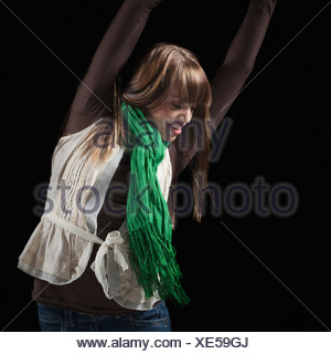 Female dancer with her arms raised above her head - Stock Photo