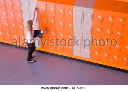 Girl opening locker in school corridor - Stock Photo