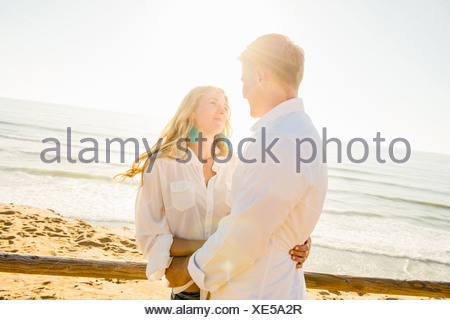 Romantic young couple with arms around each other at coast - Stock Photo