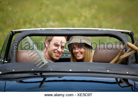 A young couple driving a black sports car with gardening tools in the back - Stock Photo