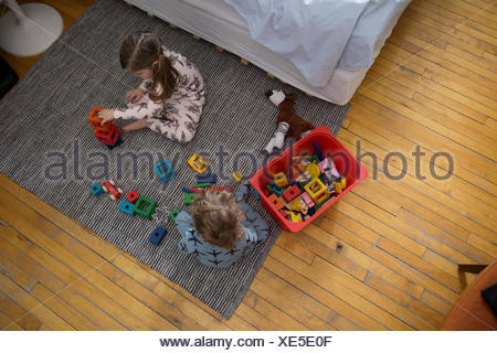 Children in pajamas playing with toys on floor - Stock Photo