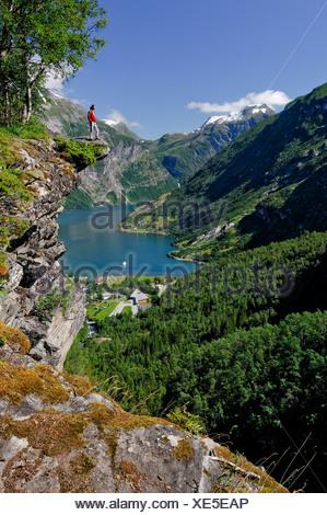 Man standing on a rock pulpit at Geiranger Fjord, Hellesylt, More og Romsdal, Norway - Stock Photo