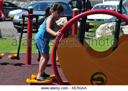 Israel, Haifa, Girl of 6 plays in a public fitness playground - model release available - Stock Photo