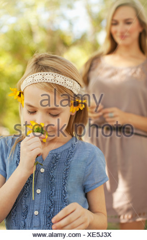 Girl smelling flowers outdoors - Stock Photo