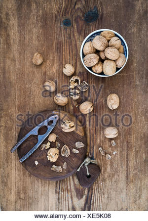 Walnuts in ceramic bowl and on wooden board with nutcracker over  rustic wooden background, top view - Stock Photo
