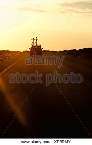 A car with two bikes on top drives towards a sunset on Antelope Island, UT. - Stock Photo