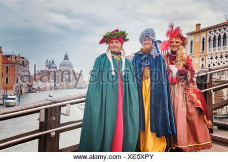 Europe, Italy, Veneto, Venice. Group of people in carnival fancy dress on the Accademia bridge - Stock Photo