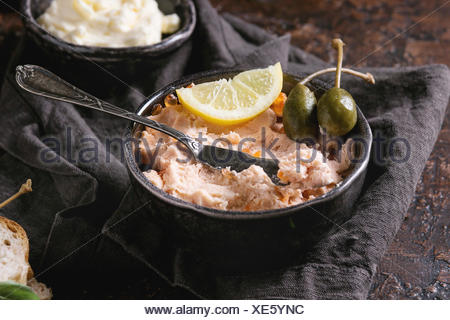 Black bowl of salmon pate with red caviar served with butter, sliced bread, capers, vintage knife and herbs on textile linen napkin over brown texture - Stock Photo