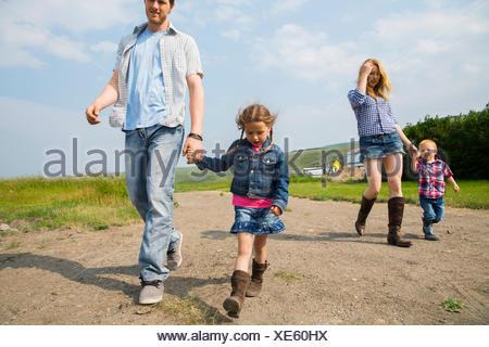 Family walking on rural dirt road - Stock Photo
