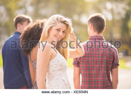 Young woman with friends in park looking over her shoulder - Stock Photo