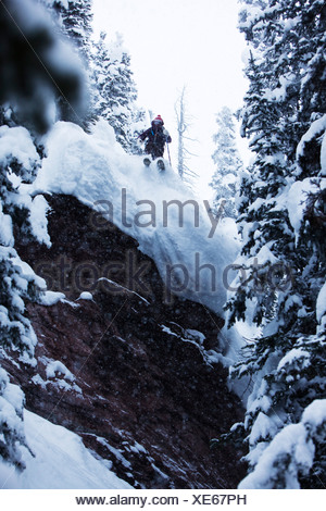A athletic skier jumping off a cliff in the backcountry on a stormy day in Colorado. - Stock Photo