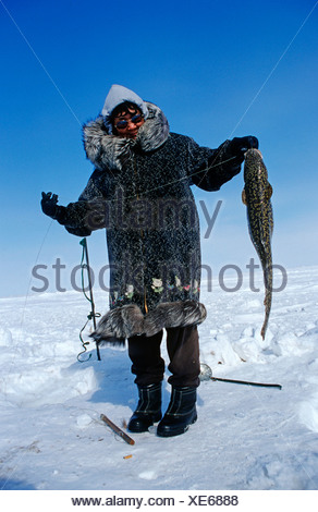 Inuit woman with a caught migratory Artic Char, Nuiqsut, on the coast of the Arctic Ocean in the far north of Alaska - Stock Photo