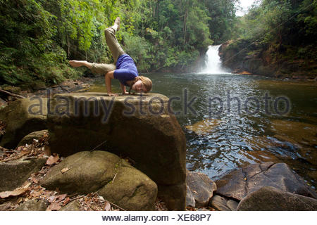 A girl practices yoga near Riam Berasap, the Falls of the Mists, which is the largest waterfall in Gunung Palung National Park. - Stock Photo