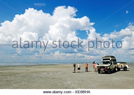Off-road vehicle with tourists on a salt lake in Nata Bird Sanctuary, Makgadikgadi Pans, Botswana, Africa - Stock Photo