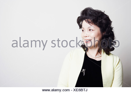 Close-up of a businesswoman looking sideways smiling - Stock Photo