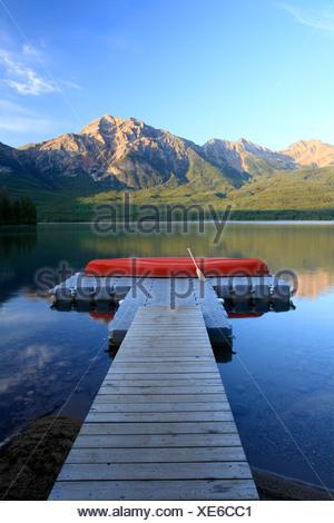 Red canoe on dock at Pyramid Lake with Pyramid mountain, Jasper National Park, Alberta, Canada. - Stock Photo
