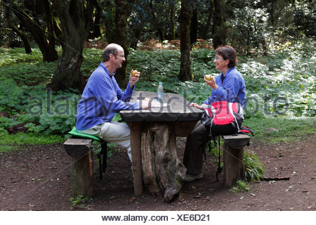 Man and woman having a rest at a wooden table in a laurel forest, Garajonay National Park, La Gomera, , Spain, Europe - Stock Photo