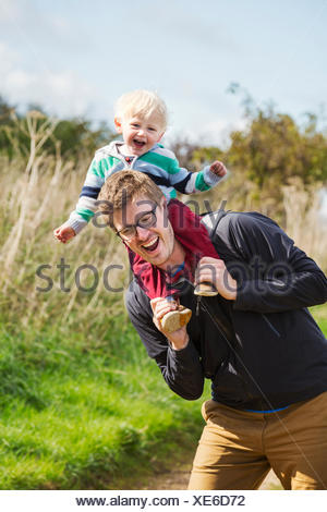 A man and a small boy on a walk, a father giving his son a piggyback. - Stock Photo