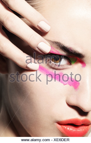 Woman smudging bright coloured make up on face - Stock Photo