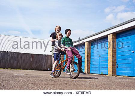 Boy giving friends a ride on bike - Stock Photo