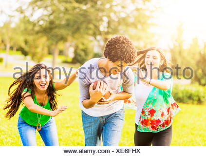 USA, Jupiter, Florida, Group of friends (14-15) playing football in park - Stock Photo