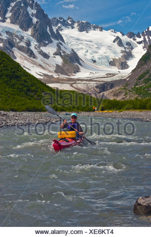 Female kayaker maneuvers down a stream in the Northwestern Fjord of Kenai Fjords National Park, Kenai Peninsula, Alaska, Summer - Stock Photo