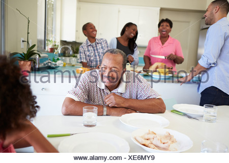 Multi-Generation Family Preparing For Meal At Home - Stock Photo