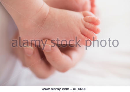 Close up of mother's hand touching baby boy's (2-5 months) foot - Stock Photo