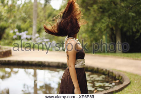 Side View Of A Woman With Blown Brown Hair By Countryside Lake - Stock Photo