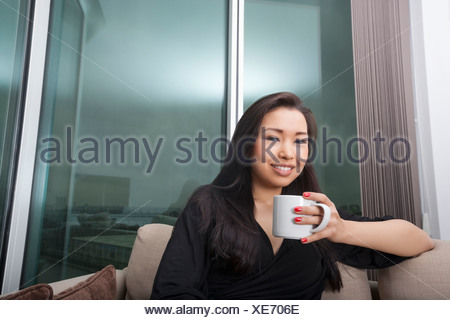 Portrait of happy young woman holding coffee mug in living room - Stock Photo