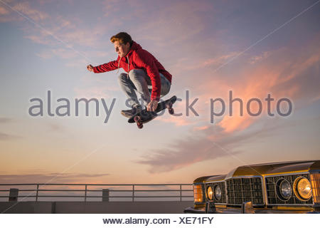 Portrait of young man on skateboard in mid air - Stock Photo