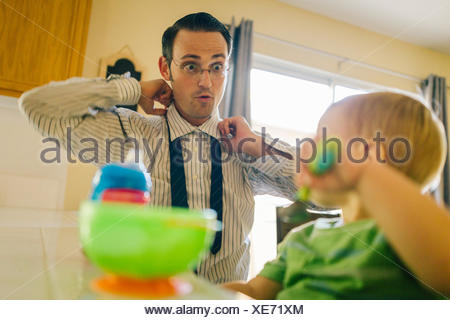 Father and young son in kitchen, father putting on neck tie whilst son eats breakfast - Stock Photo