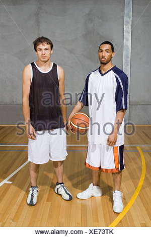 Two Young Men standing on a basketball court - Stock Photo