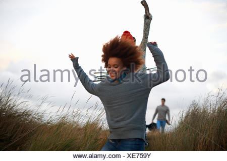 Young adults running in coastal dunes - Stock Photo