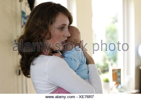 Underage mum holding child, soothe baby, hugging newborn child. - Stock Photo