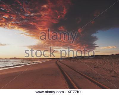 Tire Tracks On Beach Against Cloudy Sky - Stock Photo