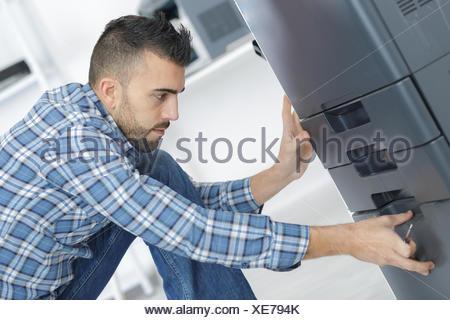 man fixing cartridge in printer machine at office - Stock Photo