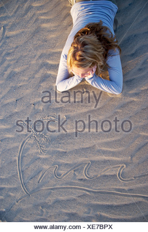 Young girl lying on the beach sand dreaming of far off places St Lucia KwaZulu Natal Province South Africa - Stock Photo
