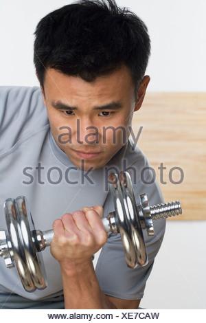 Man lifting free weights - Stock Photo