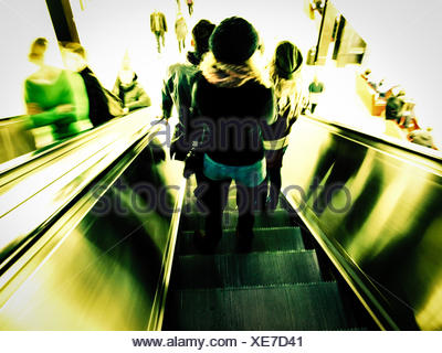 Vintage looking People going down the escalator motion blur, high key - Stock Photo