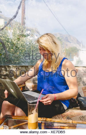 Greece, Dodecanese, Kalymnos, Woman using laptop in cafe - Stock Photo