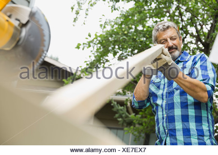 Senior man looking at wooden plank in yard - Stock Photo