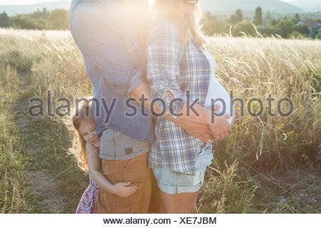 Pregnant young couple and daughter with arms around each other in field - Stock Photo