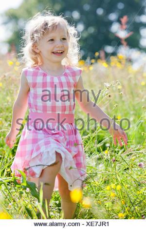 Portrait of smiling girl walking in wildflower meadow - Stock Photo