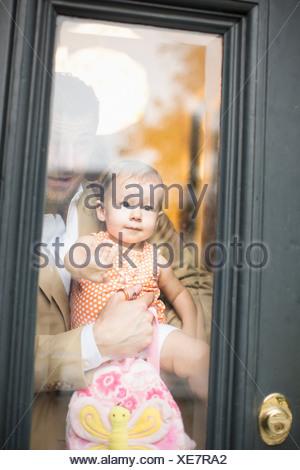 Man holding baby looking through front door - Stock Photo